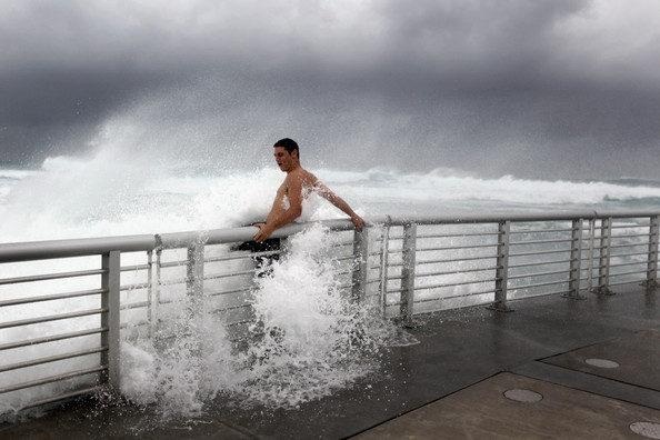 Cory Ritz braces himself as a wave bursts onto a pier at the Boynton Beach inlet from Hurricane Irene. (Joe Raedle/Getty Images)